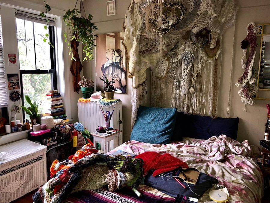 Image Description: Pictured is Dalbey's home studio and work space. Many knitted works are present both on her bed and the walls.
