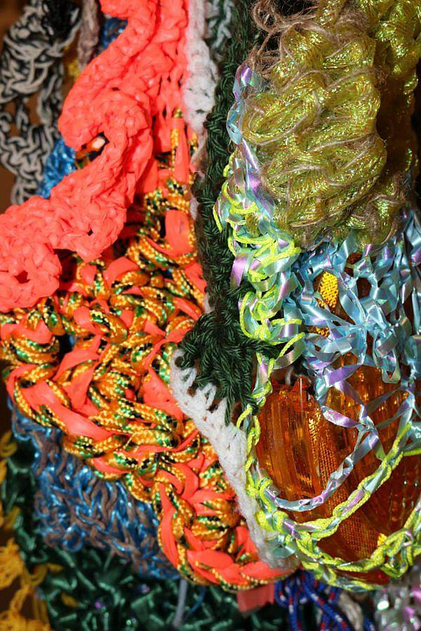 Image Description: Pictured is a small, detailed photograph of Dalbey's work. The materials featured include yarn, rope, ribbon, and found plastic that are woven together into a singular mass.