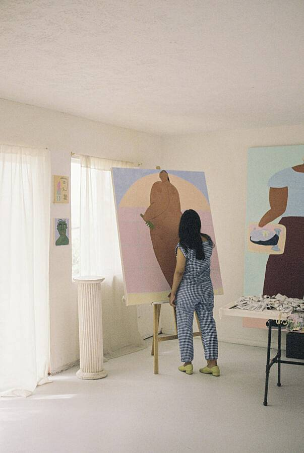 Image Description: This photograph features Martinez working in her studio. Martinez is working on a large painting on an easel accompanied by her other works in a white room with sun shining through the drapes. Martinez is wearing a plaid pair of pants and matching top paired with green shoes.