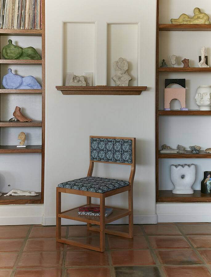 Image description: This photograph features a furnished  domestic scene. The walls are white and the floor is made up of glossy brown tiles, a single wooden chair with blue sun upholstery is set between shelves of ceramic objects and vinyl records.