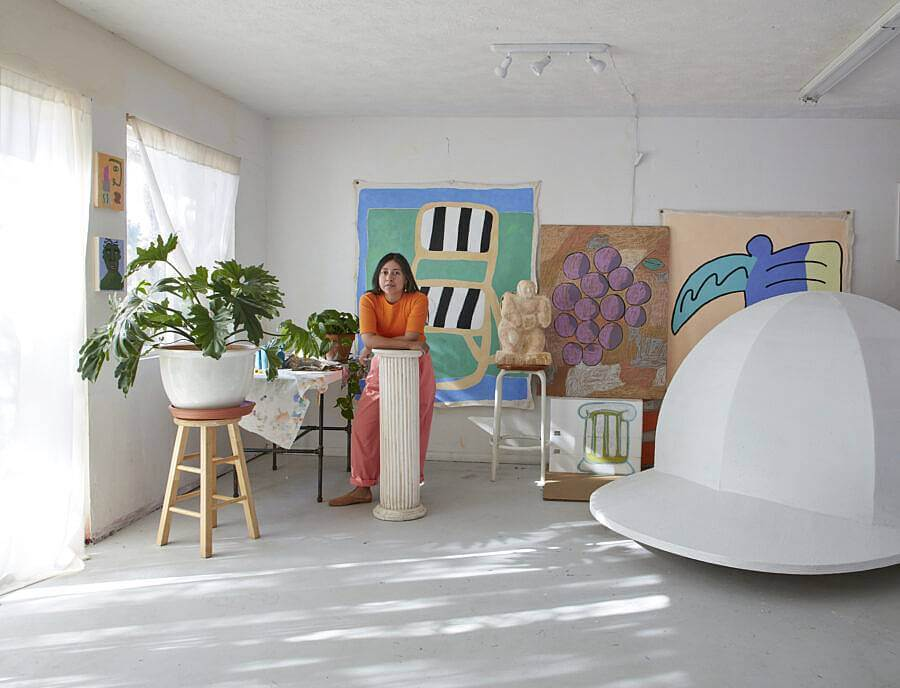 Image description: This image features Martinez in her studio with some of her work. On the wall behind her are un-stretched canvases, a large sculpture resembling a baseball cap, a pillar that Martinez is leaning against, and a houseplant on a stool.
