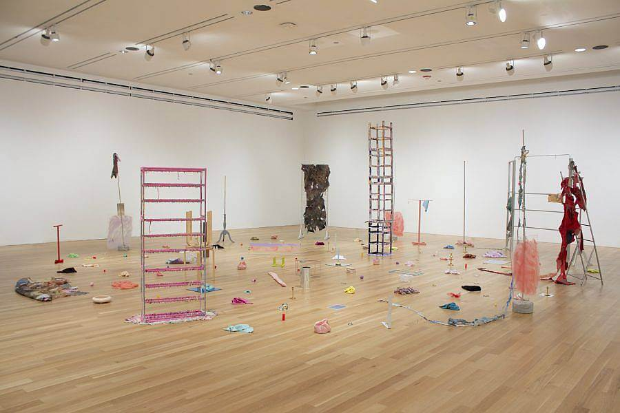 """Image description: This is an installation shot of """"Wet, Wasted Afternoon"""", and exhibition held at Logan Center Exhibitions in 2019. The image shows various sculptures made from objects like furniture, household items, and textiles, many of which are painted pink, turquoise, yellow, and red."""