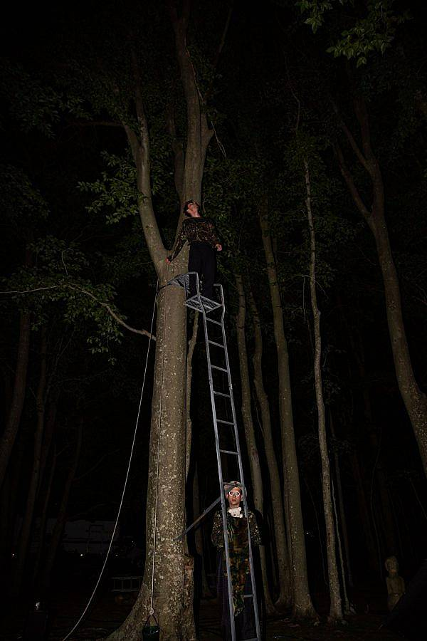 Photography of composer BIlly Bultheel and Alexander Iezzi. It is nighttime in the woods and stands at the top of a long metal ladder that leads to a blind. Alexander Iezzi is on the ground peering through to bars on the ladder.