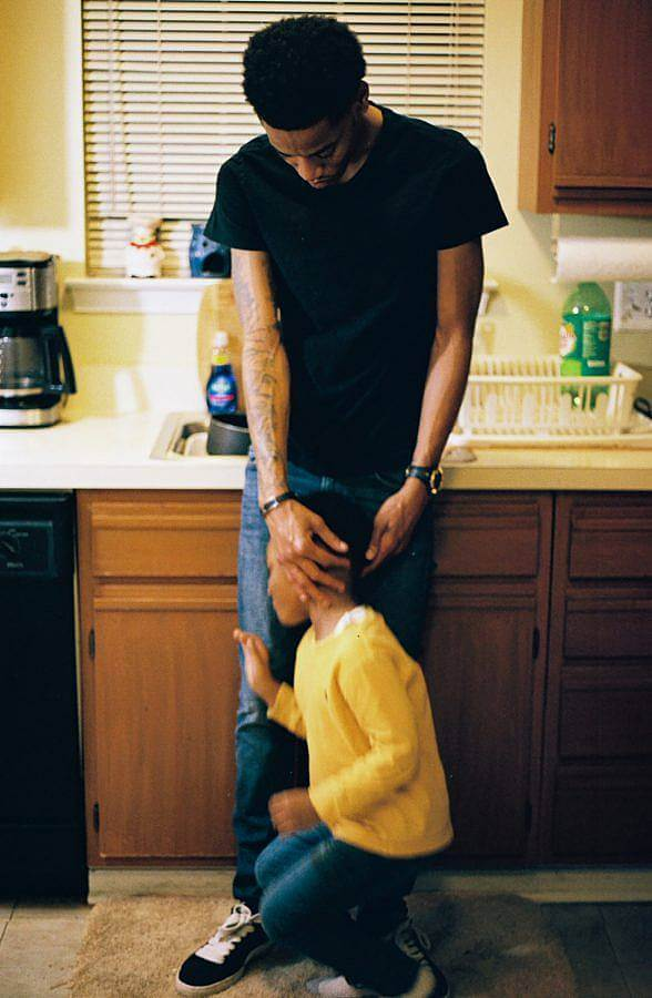Image Description: This is a photograph of a father in a black t-shirt standing in front of a kitchen sink. There is a young child in yellow in front of him and the father is reaching down to try and calm him to be in the picture.