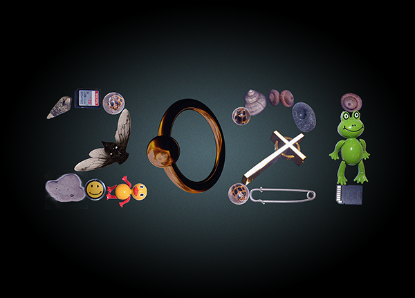 "The number ""2021"" is spelled out using various cropped images of objects including a safety pin, a toy frog, numerous shells and marbles, a smiley face, a cicada, and a rubber duck. These are all true to color against a black background, the center of the background is a soft grey to highlight the number 2021."