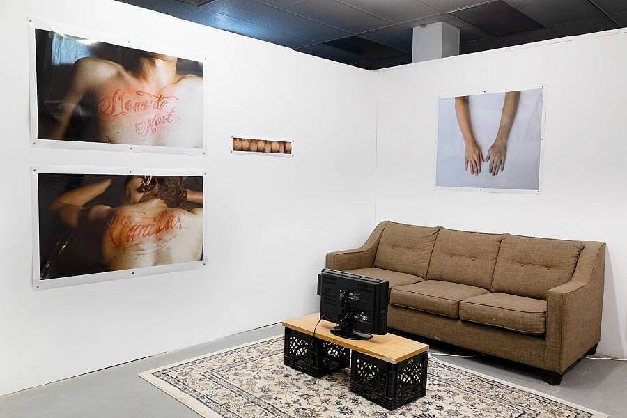 The corner of an exhibition is on display. There are two white walls, against the right wall is a tan mid century couch. On the ground a repurposed oriental rug. Atop the run is a small old flat-screen tv is on a wood plank held up by milk crates. On the Right wall is a photography of outreached hands. On the left are two large photographs of tattoos in red ink on someones chest and back. Next to this is a photostrip.