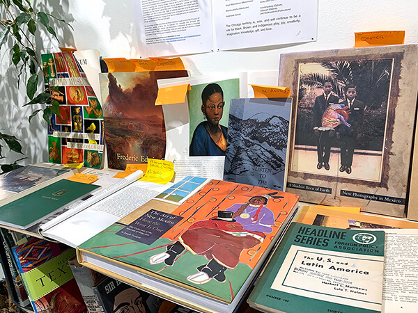 A variety of books of all different coors, several of them green have orange sticky notes sticking out from them. Several of the books are turned open to the sctions that are sticky-noted. The center book features an illustrated woman with black hair and a strong forehead. Behind her is a light green background.