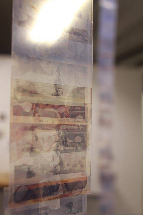 Image Description: This is documentation from a larger installation of floor-to-ceiling reels of layered deteriorated prints. This is a detail shot of one of the reels. The images are in shades of tan and printed on a transparent material.