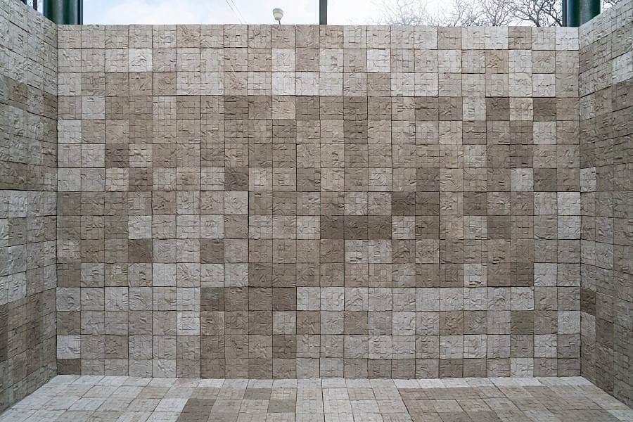 Installation view of cement tiles that make up a room. The walls and floor are both made of a serialized cement tile structure.The back wall is on display. The tiles which are textured with the skin of human donors, are 6 inch squares. The walls are 17 squares high and 25 squares across. A window can seen behind the wall.