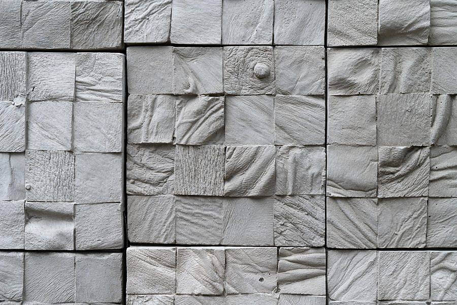 detailed image of multicolor grey toned cement stones that show casts of human skin on small tiles.