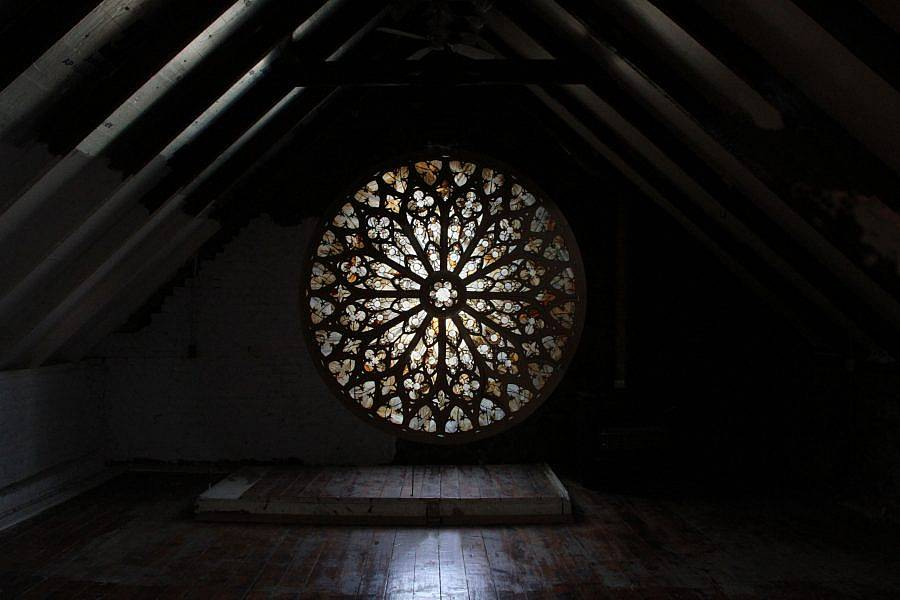"""View of a circular """"Glass paned window,"""" formed by dried lettuce. The window is at the back of a attic space. Light shines through it."""