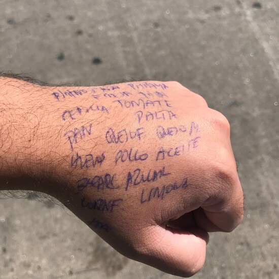 "Photo of artist's hand above a grey cement pavement. There is blue lettering on the hand. It is a grocery list in spanish. The visible words going from left to right read as 'PINTO,TOMATE, PAN,PALTA, QUESO F, QUESO M, HUEVOS, POLLO, AZUCAR, LIMON."" There are other words as well, they are not all readable."
