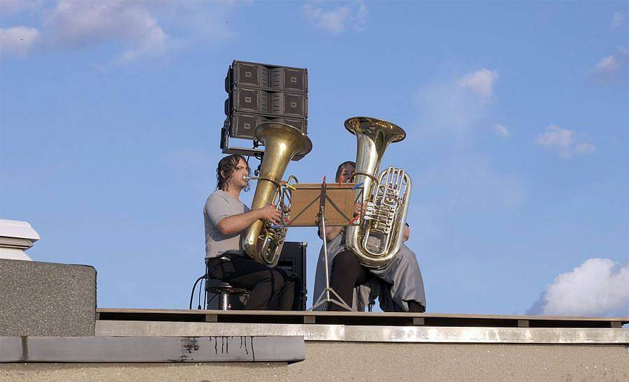 Photograph of two tuba players on roof top of a building. A blue sky with sparse clouds in visible behind them. The sun shines on their face..