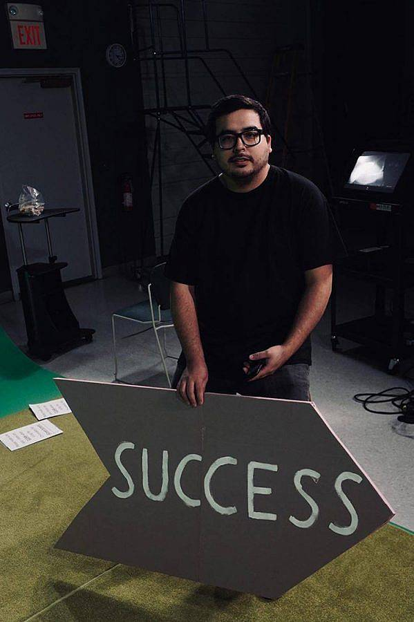"Colored photography of artist Gonzalo Hernandez. He is pictured in a black shirt with black glasses on a green carpet near a green screen. He holds a large arrow sign that reads ""SUCCESS."""