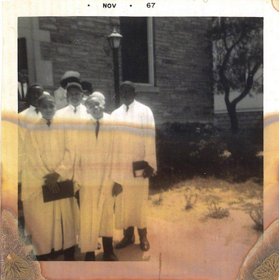 Image Description: This is a photograph from November of 1967. There is a group of five young boys in white robes for their confirmations standing to the left of the image. They are standing in a garden with a stone building and a lamp post behind them. The photograph itself is deteriorating.