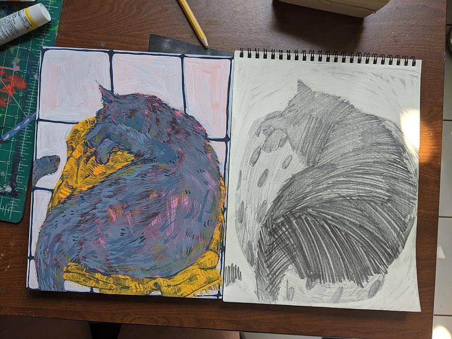 Image Description: This is an aerial photograph of the artist's desk, showing the same painting and drawing of a sleeping cat. The cat is hiding it's face and in the painting to the left, the cat is painted in blue-grey tones and is sleeping on a yellow bed.