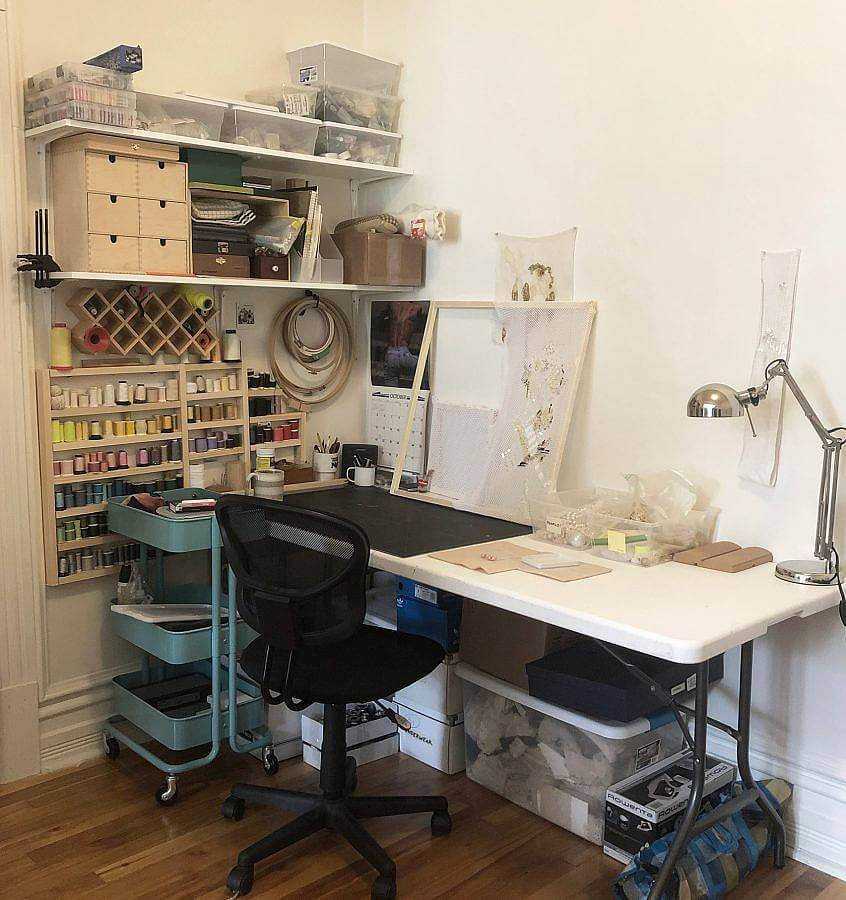 Studio of the artist depicted. Shelves include spindles of thread, boxes of sequins and more. A desk and chair is also depicted.