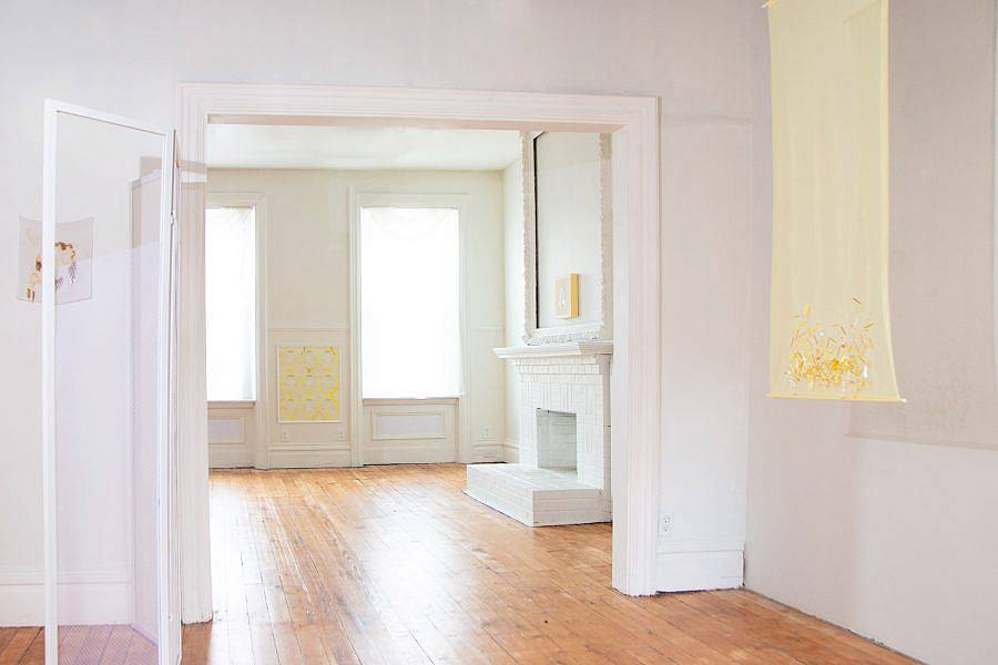 Installation view of Indecent Exposure. A yellow translucent partition hangs from the ceiling, various works are visible and and installed along the walls. An arch way is depicted which leads to another room and fireplace.