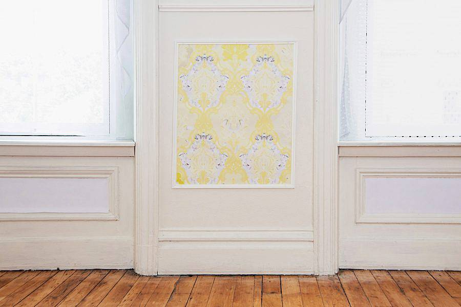 Detailed shot of artist's exhibition Indecent Exposure. The photo shows an image of a wall between two images. On the wall is rectangle of an ornate yellow wallpaper.