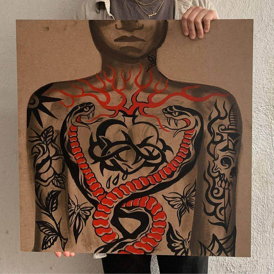 A person holds up a painting. The painting uses latex paint on masonite. It features a tattooed person. The chest has a heart tattooed on it, with thorns encircling it, red flame line work extends outside it. Two snakes encircle the heart. Other tattoos of skulls and butterflies are on the person's arms.
