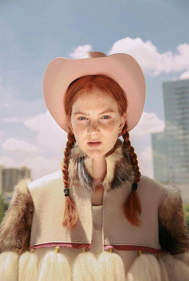 Photograph of a red-haired white feminine person outside. They wear a pastel pink cowboy hat, their hair is in braids, and they have on a fur coat, which has a fur color, shoulders, and the rest is a suede material. There are also white tassels of brushed out hair visible. Behind them are sky scrapers and a partly cloudy sky.