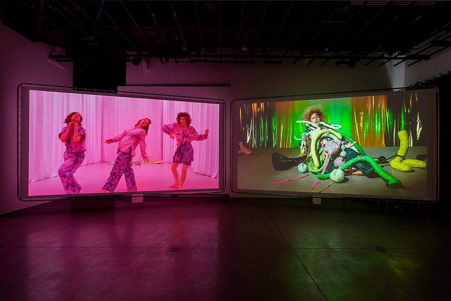 Image of two-way video installation. On the left a video of three performers in a pink curtain background dance. In the left screen is a performer, a gold curtain background is behind them. A plethora of objects are placed upon them and are apart of them. Green lights are used in this video.