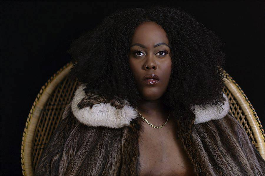 Photo of Darryl DeAngelo Terrell's alter-ego Dion. They have voluptuous curly black hair. They are wearing a fur coat, with a white fur collar, they sit upon a peacock wicker chair.