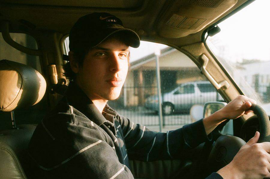 Dan wears a black baseball cap and a stripped polo long-sleeve shirt while driving in the front seat of a Toyota. The sun shines through the front window onto Dan's face.