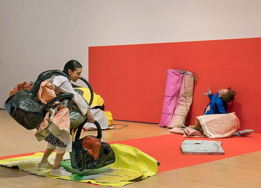 Performance with two performers, red background on wall, and orange rectangle are on floor. In foreground, one performer with their hair slicked back has multiple bag-like made objects on their body/apart of their body. They pick up another. In the background to the right is the second performer, their back extended backwards and they are wrapped in fabric against the red wall.