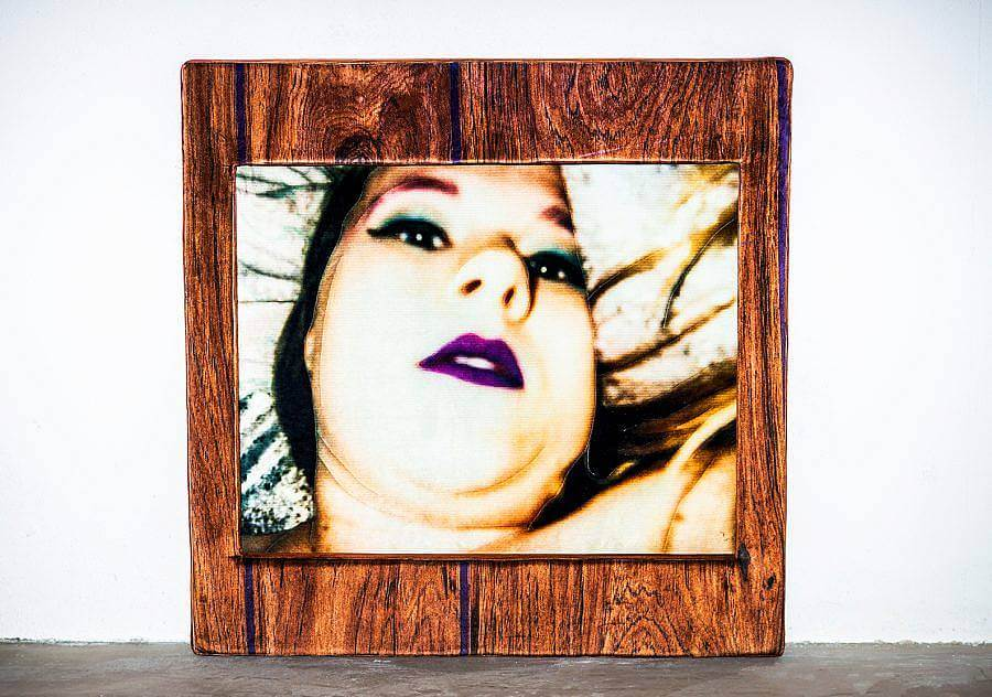 A close of image of artist Sarah C Blanchette of her face, lips, chin, against a pillow. The image is framed by a wood panel.