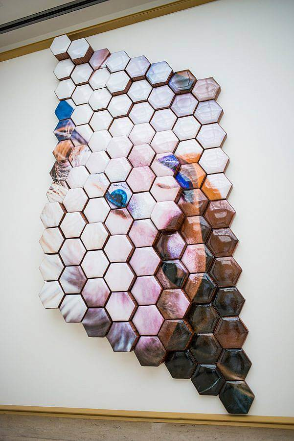 Hexagon fabric shapes form a rhombus. They are arranged in varying depths. An image of the portrait of the face of the artist is displayed upside down. She wears purple lipstick. Her eyes are saturated blue.