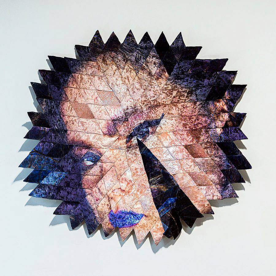 An image of a woman is displayed in a series of diamond shaped iridescent velour fabric pieces. The fabric pieces form a circular form, with their points, pointing outward.