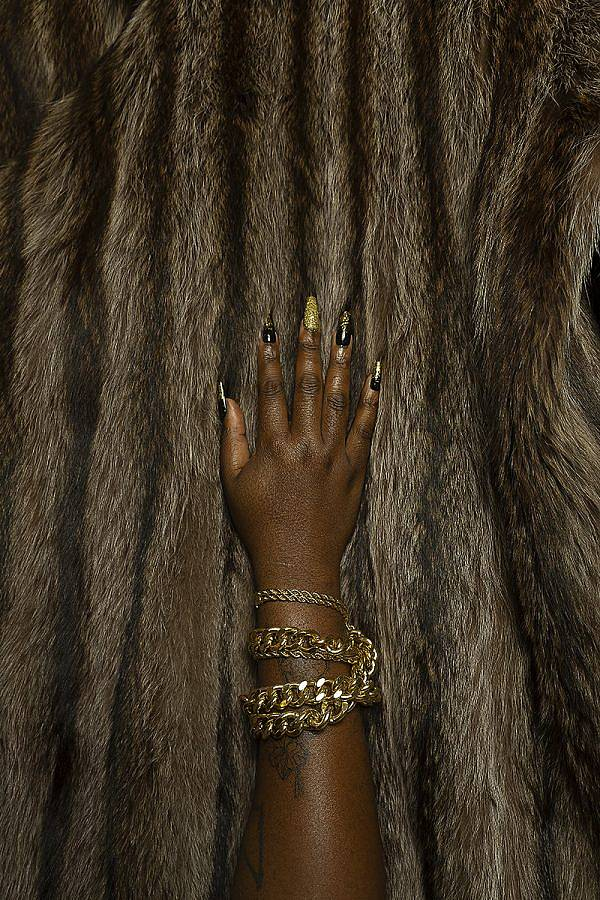 An image a hand of a black queer person grazes fur. The hand has black and gold coffin shaped acrylic nails. The middle finger nail is gold all over. Gold bracelets and gold chains are placed around the wrist.