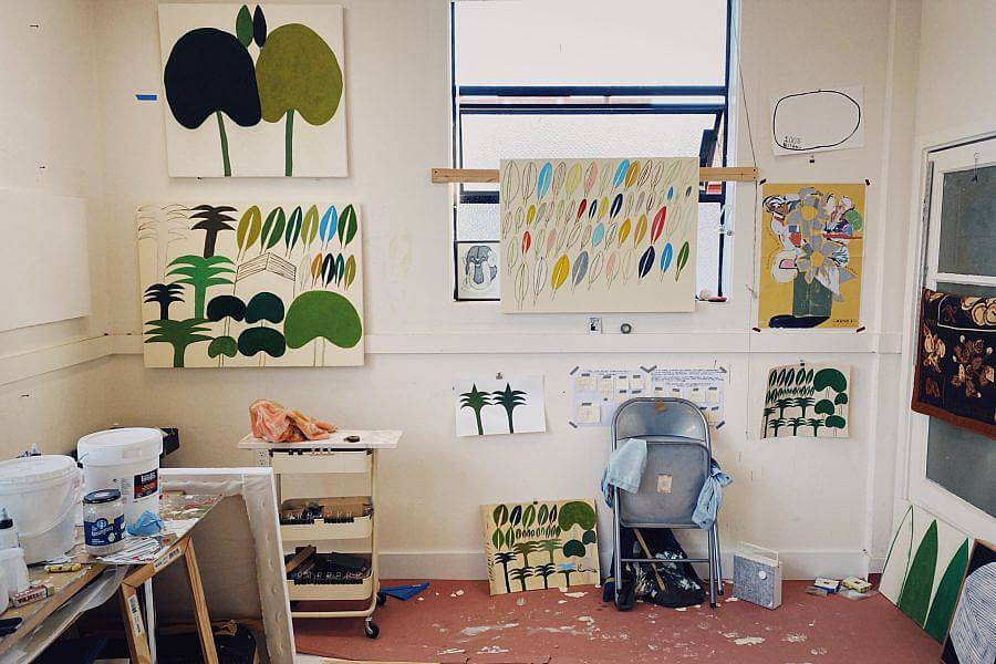 Photograph of Ryan Whelan's studio, features paintings of his hung on the walls, painting supplies and a metal folding chair.