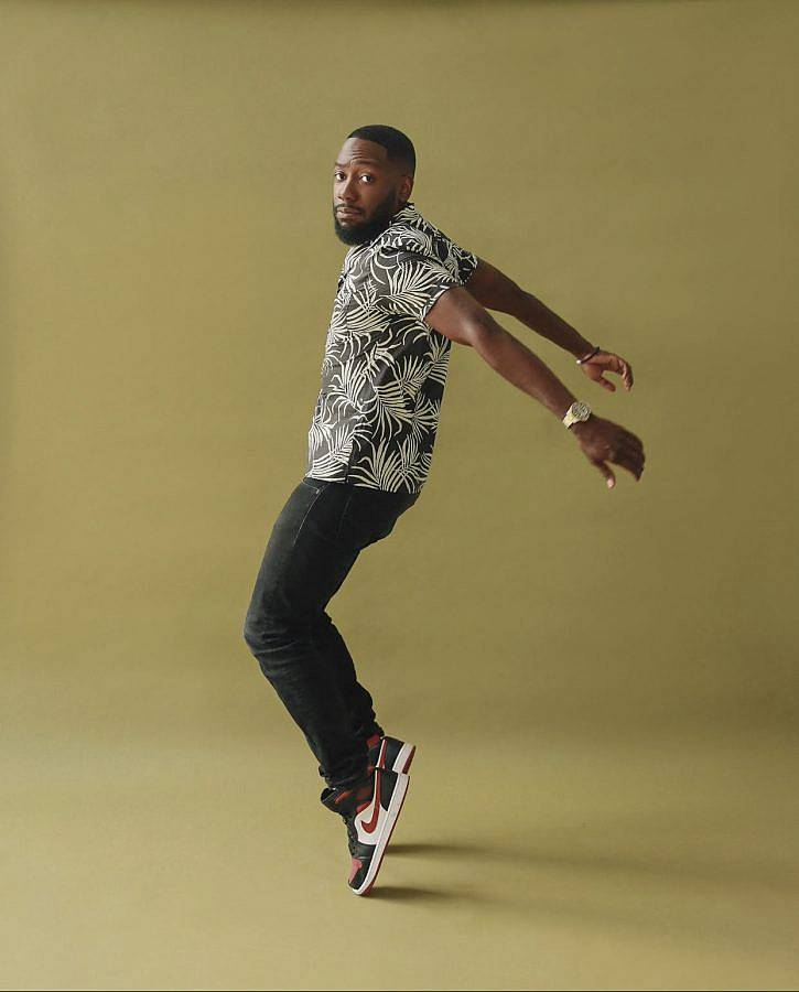 Editorial photography of actor Lamorne. Photo of a black man in a toe stance against an olive background. He wears nike shoes and a patterned top. He has a trim beard and his hair is cut close to his head.