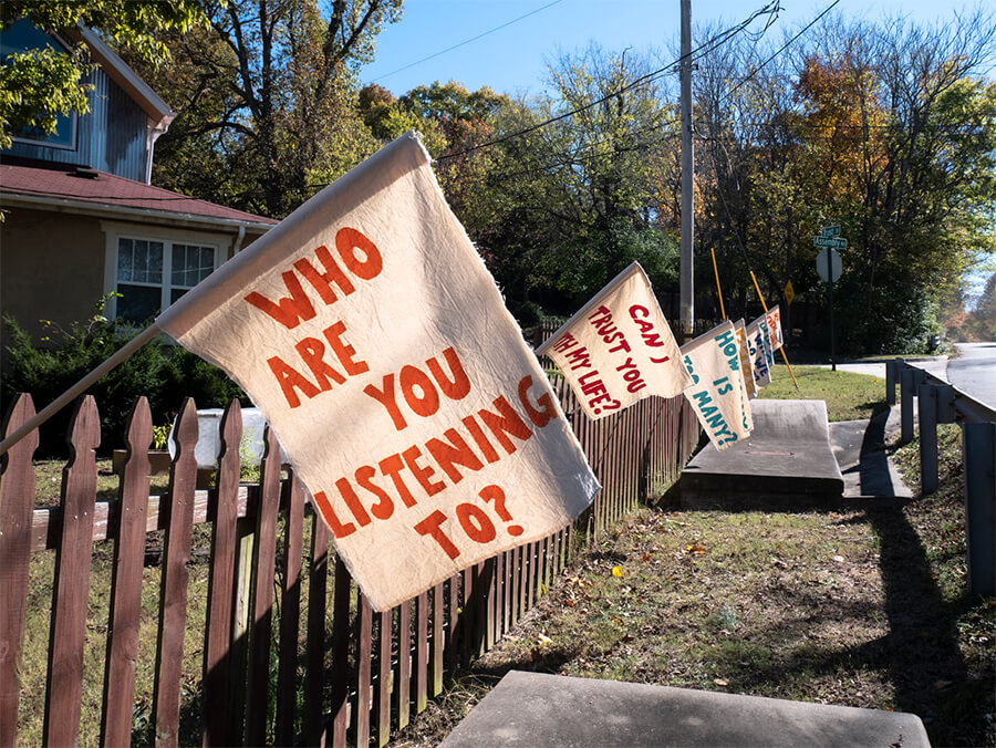 "A series of flags are hung off of a wooden Fence. The one closest to the viewer reads, ""Who are you listening to?"" , The other about 20 ft back reads ""Can I Trust You with My Life?"" There is grass around the fence, trees in the background, and a blue sky."