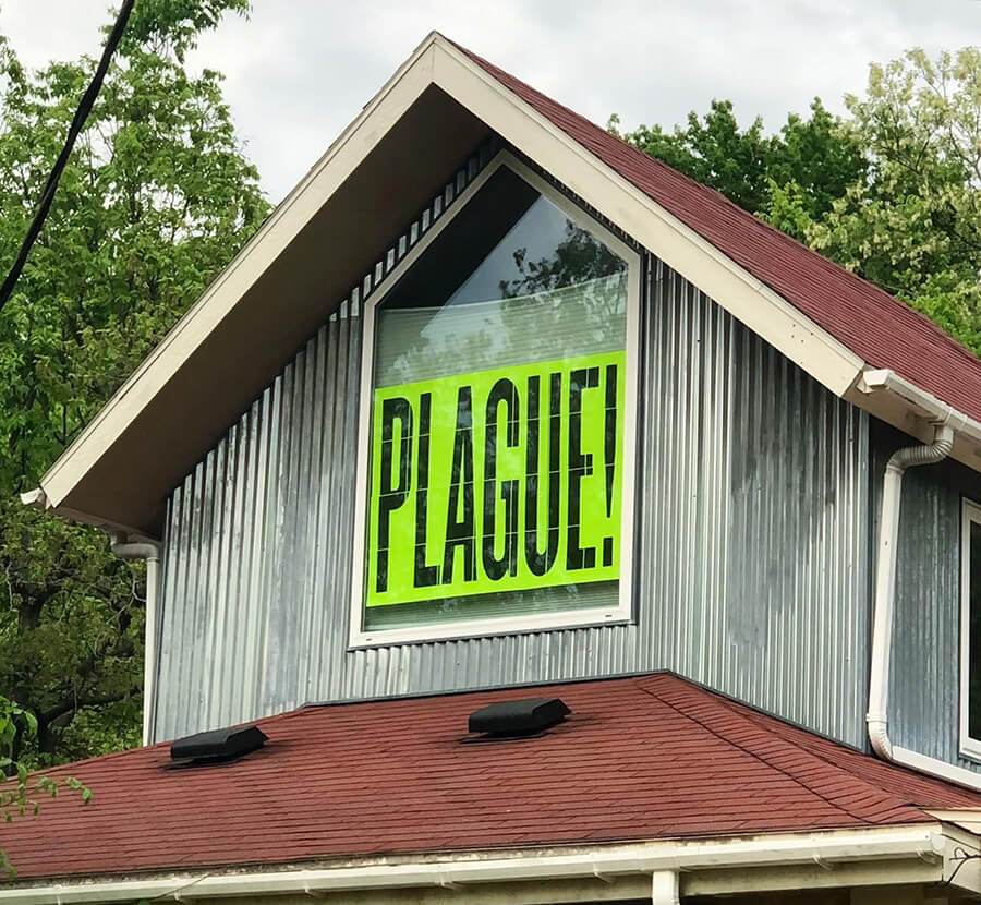 "Photo of a two story house. Focused in on a center top window. In the window is a printed sign that says ""PLAGUE!"" in all caps, it its bolded against a green sheet. The sky is visible behind the house."