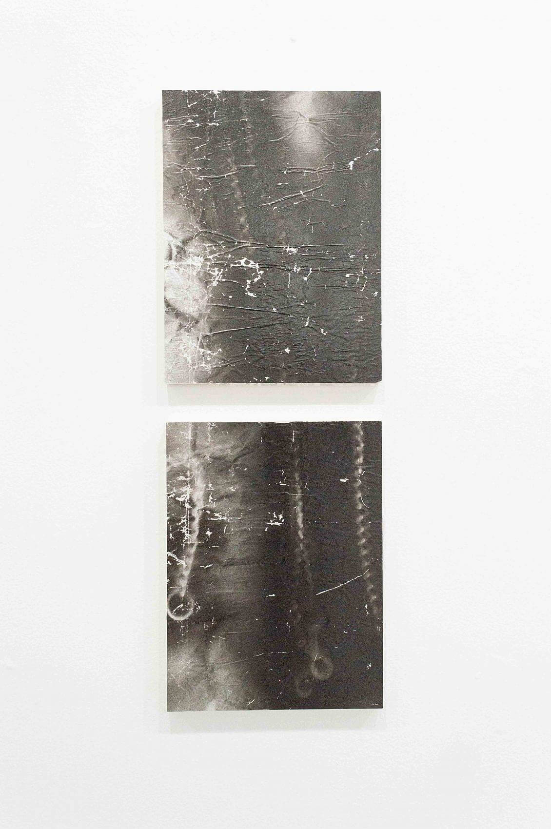There are two rectangular panels stacked vertically. The images are of blurred chains with hooks on the end and the top image leads into the bottom. They are in black and white and the surface is wrinkled.