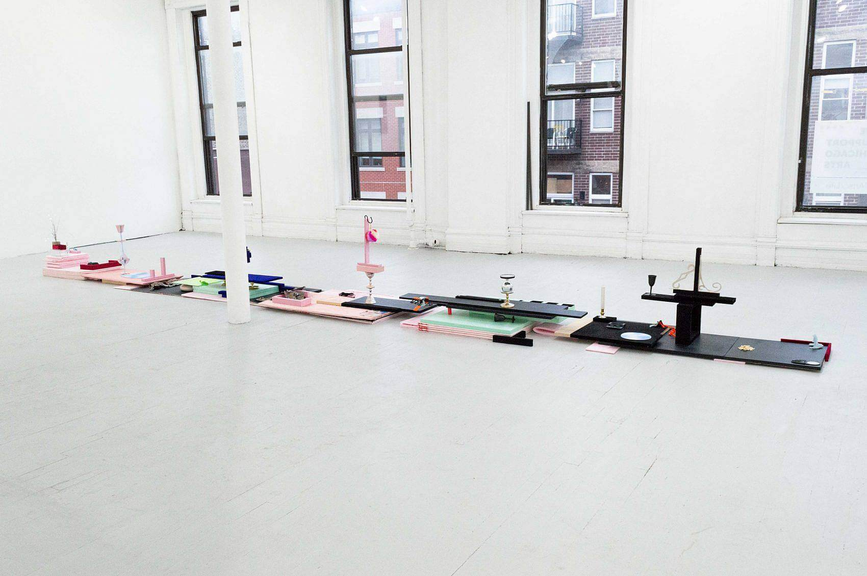 There is a long, low, and narrow sculpture sitting on the floor. There are various stacks of of light pink, green, and black insulation foam topped with various small objects like tinsel, small blue towels, compact mirrors, rhinestones, or small makeup sponges. There are also many small velvet blocks in blue and red.