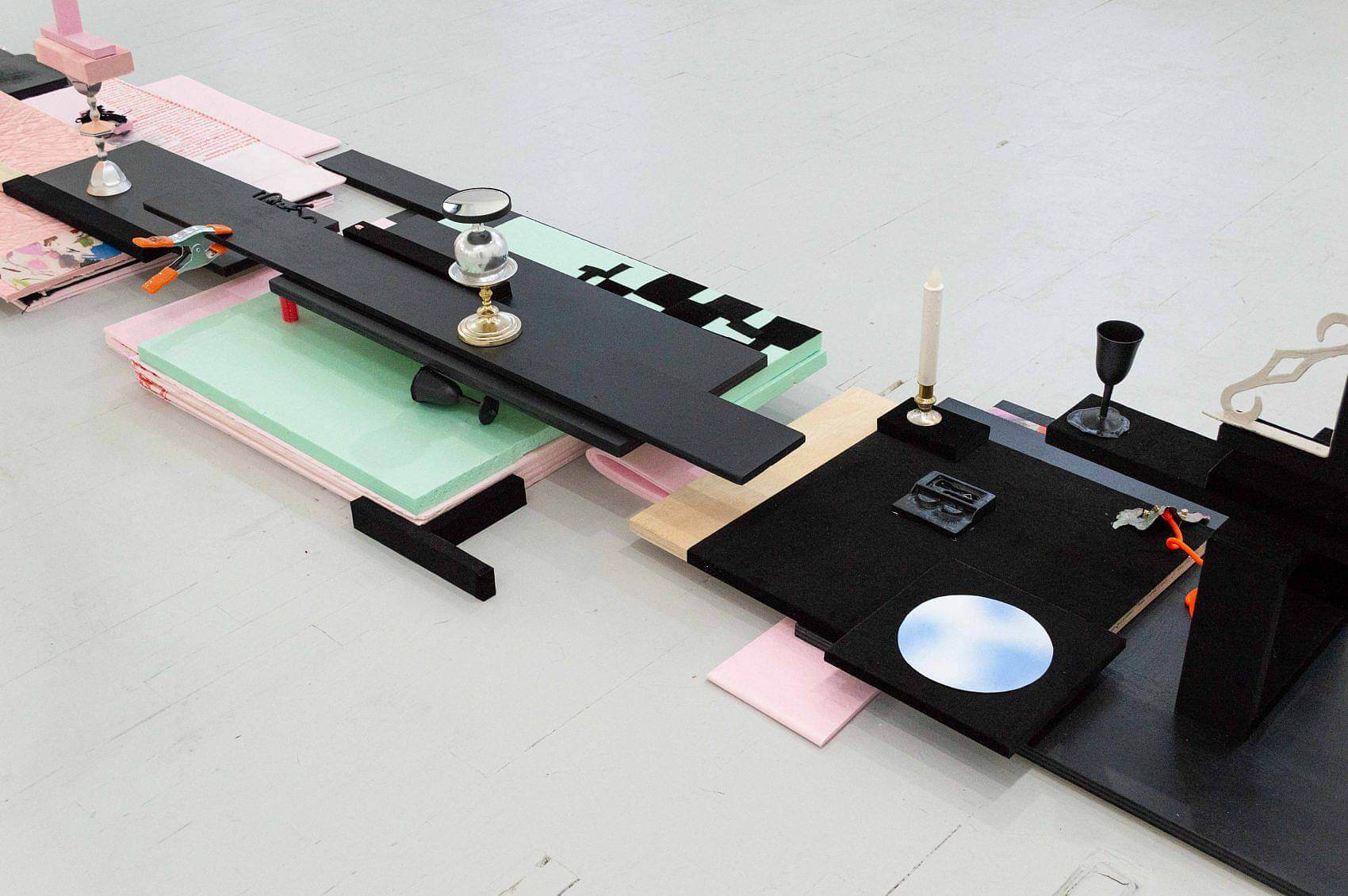 Stacked on the floor are pink, green, and black sheets of foam of various sizes. Arranged on top is an open contact mirror, an orange and silver clamp, two small black wine glasses, an electric candle, and a florescent orange cord. Also arranged on the foam is an irregular grid made from pieces of black velvet and a circle of sky blue with white clouds.