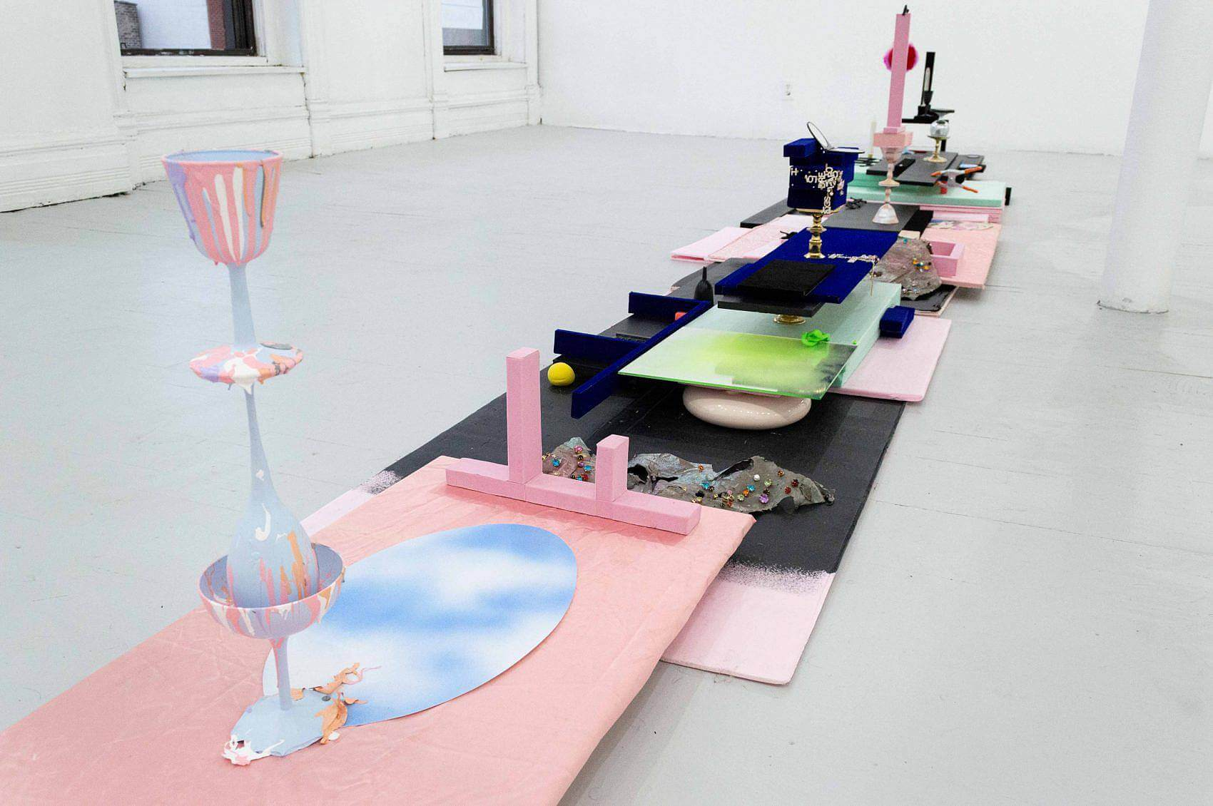 There is a pink sheet of foam wrapped in pink fabric. There is an oval sheet of paper displaying a blue sky with clouds laying on top. There is also a stack of three different light blue wine glasses with dried pink, orange, and white painting going down the sides.