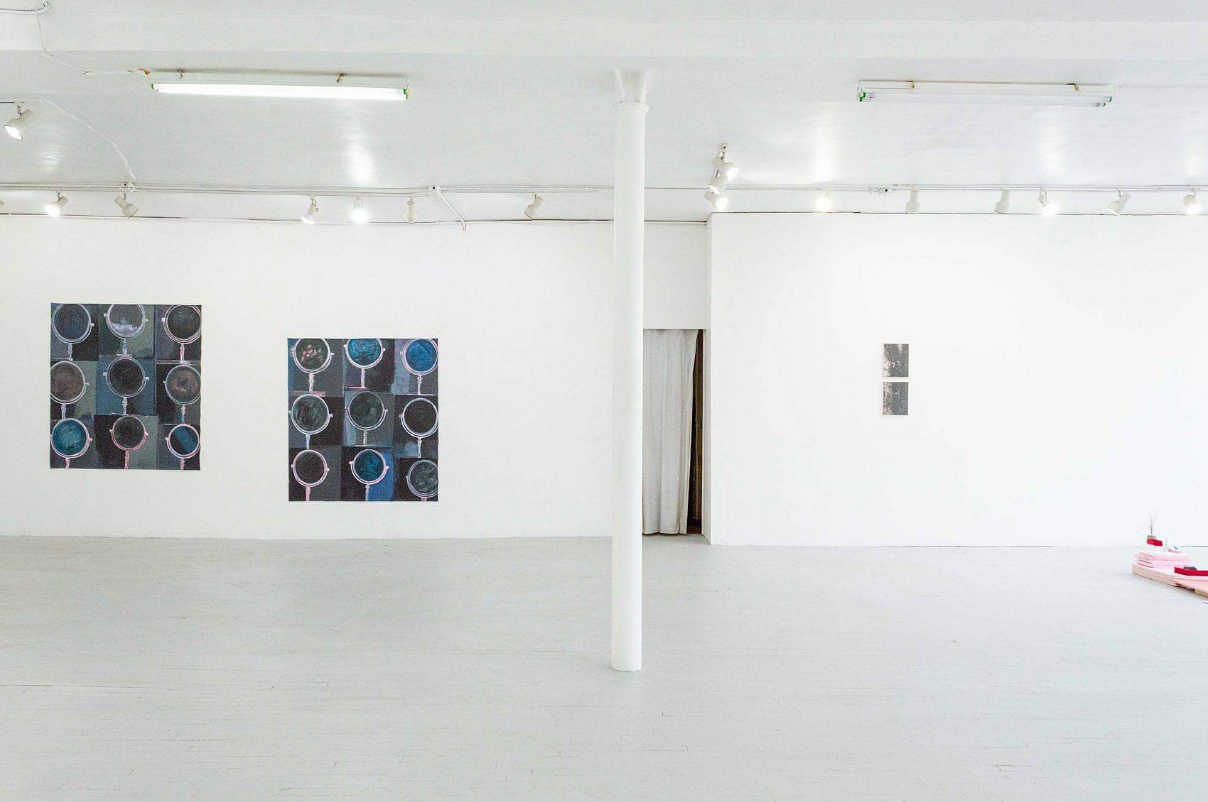 This is an installation shot of the exhibition. To the left of the pole in the center of the room are both paintings from Madeline Gallucci's
