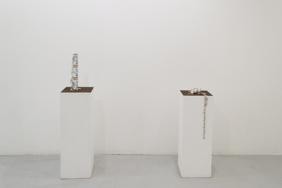 There are two white rectangular tall vertical pedestals side by side. Both are topped with a fine layer of dirt. On the left pedestals is a stack of three cans with a chain of silver soda can tabs coming down on to the surface of the pedestal. On the right pedestal, there is one can laying on it's side with tan powder coming out of the top. There is another chain of silver soda can tabs coming from the center of the can, off the side, and down the pedestal.