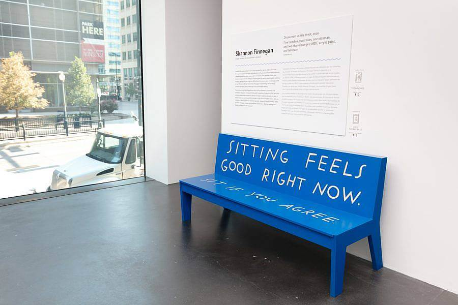 "Image description: A blue bench that says, ""Sitting feels good right now. Sit if you agree."" Behind it is wall text with the heading ""Shannon Finnegan."" To the side is a window looking out on downtown Denver."