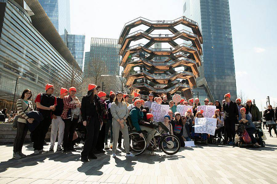 Image description: About 40 people posed in front of the Vessel sporting neon orange, Anti-Stairs Club Lounge beanies and holding Anti-Stairs Club Lounge Signs.