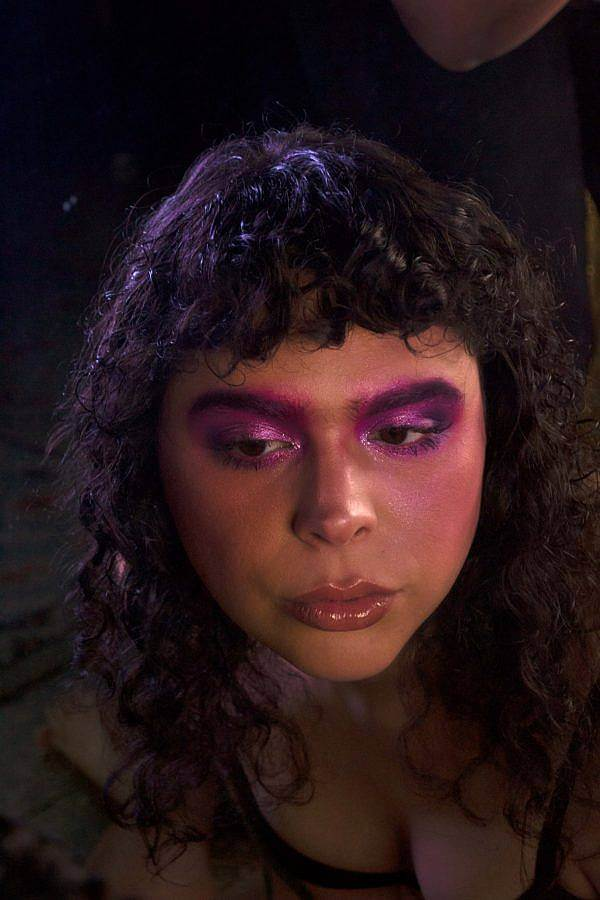 Photo of DJ Ariel Zetina, an olive skinned woman with curly dark brown/nearly black hair. It is a darkly lit photo with a spotlight on her hair and face. She wears saturated purple and pink make up on her eyes and a light glistens off her curly hair.