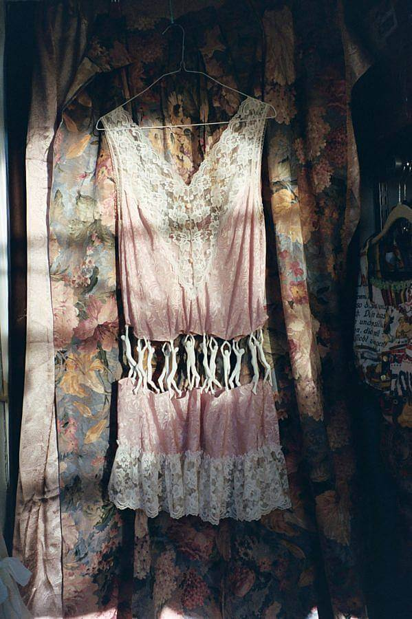 Image description: A lace lingerie dress is photographed in natural light against a vintage flower tapestry. In the middle of the dress a series of plastic clinging men figures hold the piece together.