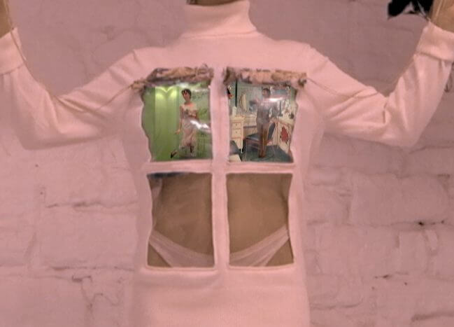 Image description: A still from Martina Cox's ad campaign. A model with pale skin wears a turtleneck dress with a window pane in front. In the top two panes of the window a series of video displays project.