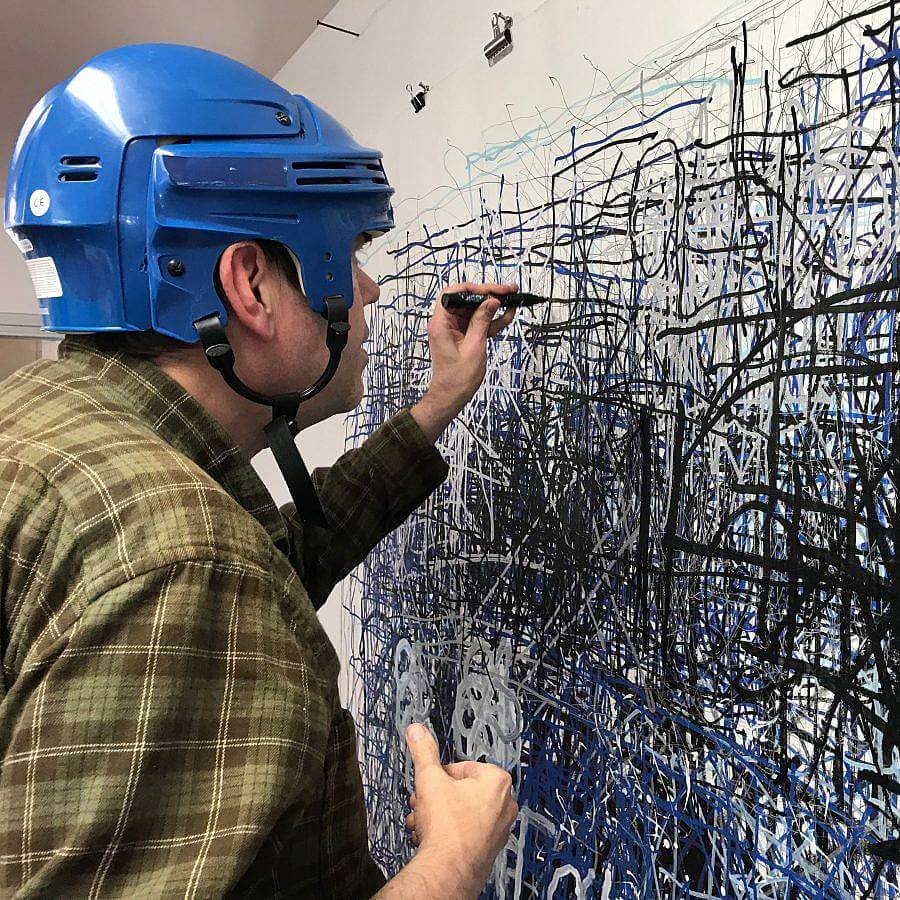 Image description: Artist Dan Miller wears a blue protect helmet and an olive green plaid shirt. He is using a black marker to make marks on a large white surface. We can see the profile of his face.