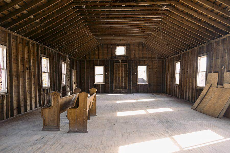 Image description: A stripped down all wooden interior of a building is displayed. Natural light pour in through the windows. Two church pews are on the left.